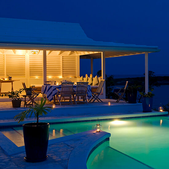 The infinity pool at Little Whale Cay lit up at night