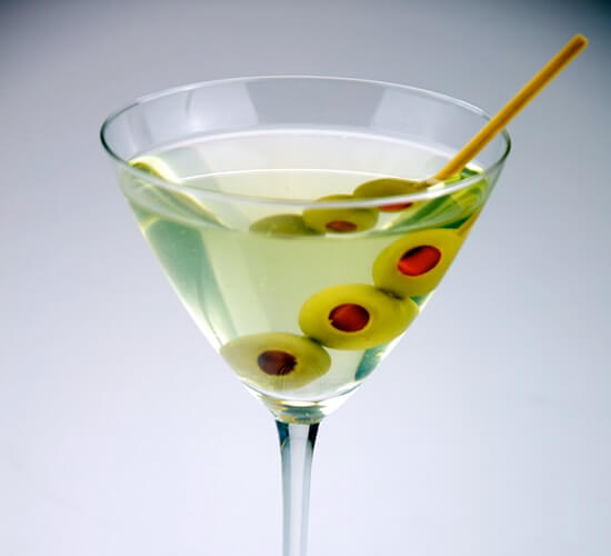 Triple olive Dirty Martini shot on a white background.