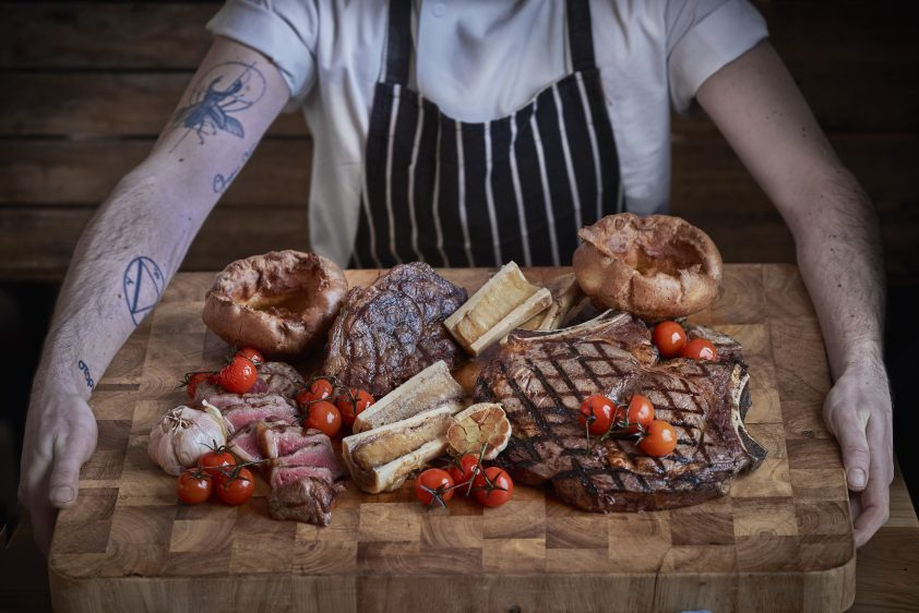 Chef presenting steak at Gillray's Steakhouse and bar