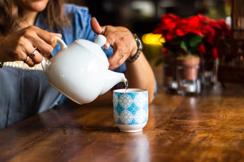 Woman pouring freshly brewed tea