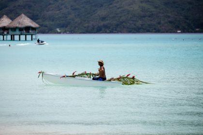 Happy Polynesian on the pirogue decorated for wedding. Island Bora Bora.