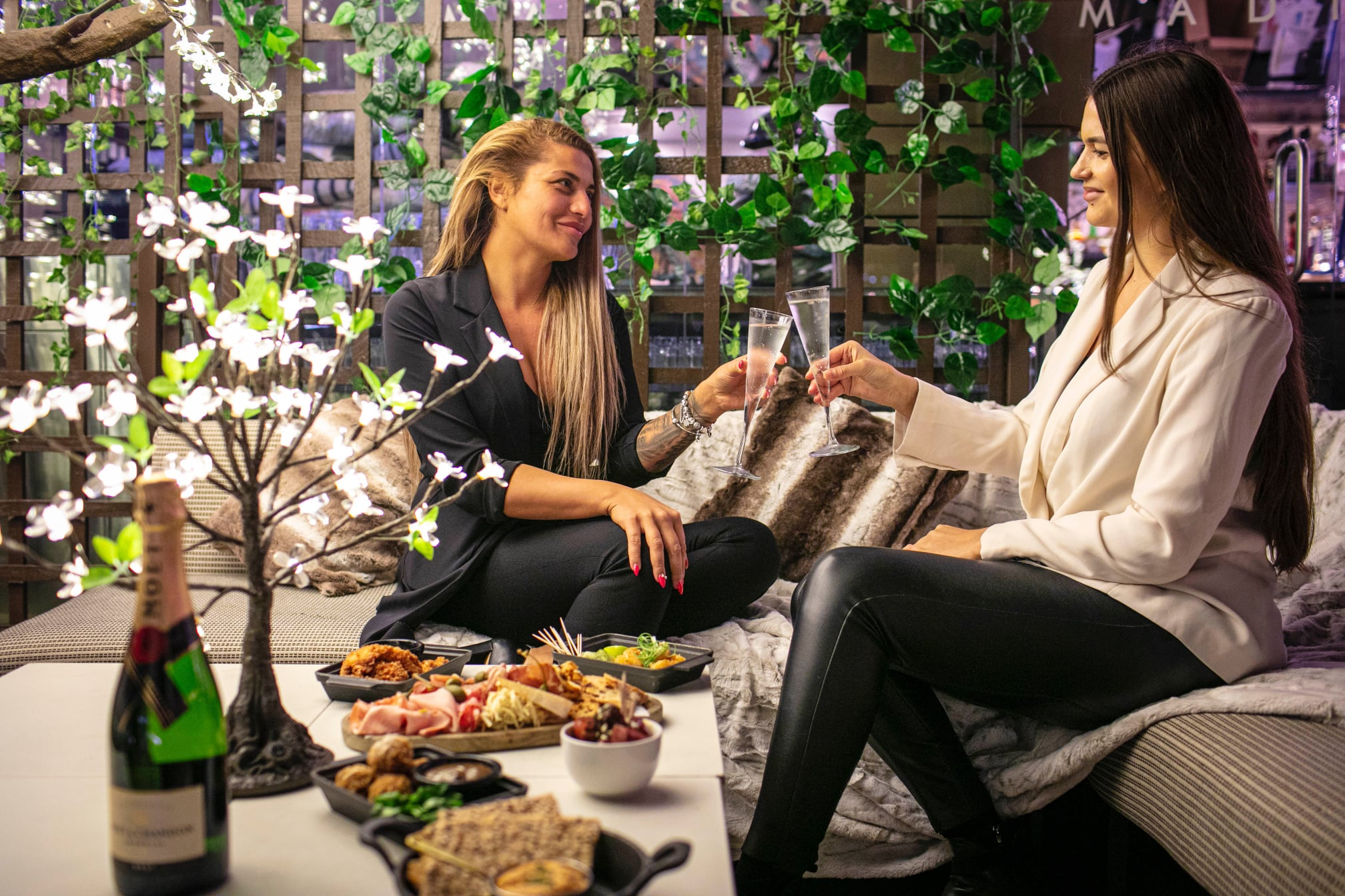 Two women enjoying champagne and canapes at Madison