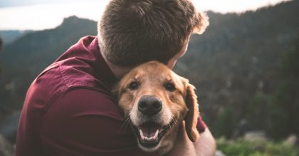 Man hugging dog as act of kindness