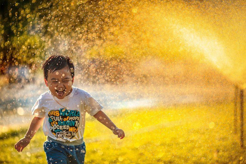 Laughing boy running through water