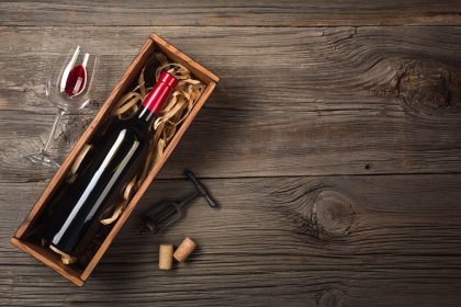Red wine in a wooden wine box with a glass and a corkscrew on a wooden table.