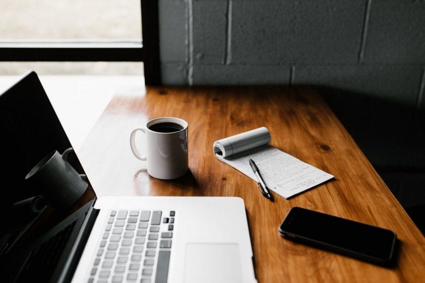 laptop, mug and phone on table