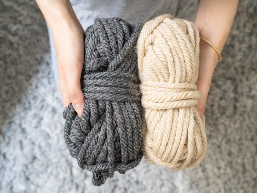 Woman holding grey and beige chunky wool yarn
