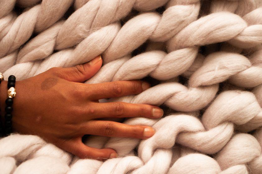 Hand feeling a soft big knit blanket