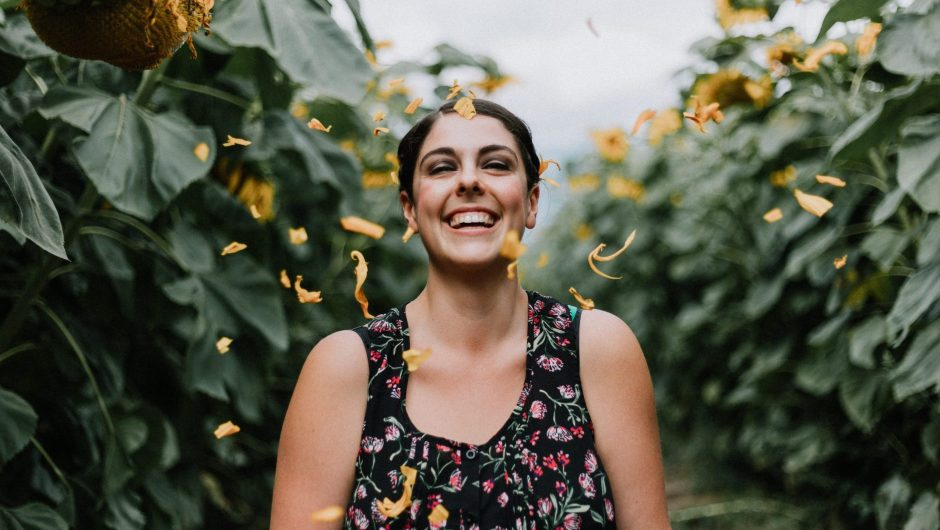 Happy smiling woman in field of sunflowers