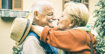 Happy senior retired couple having fun kissing outdoors