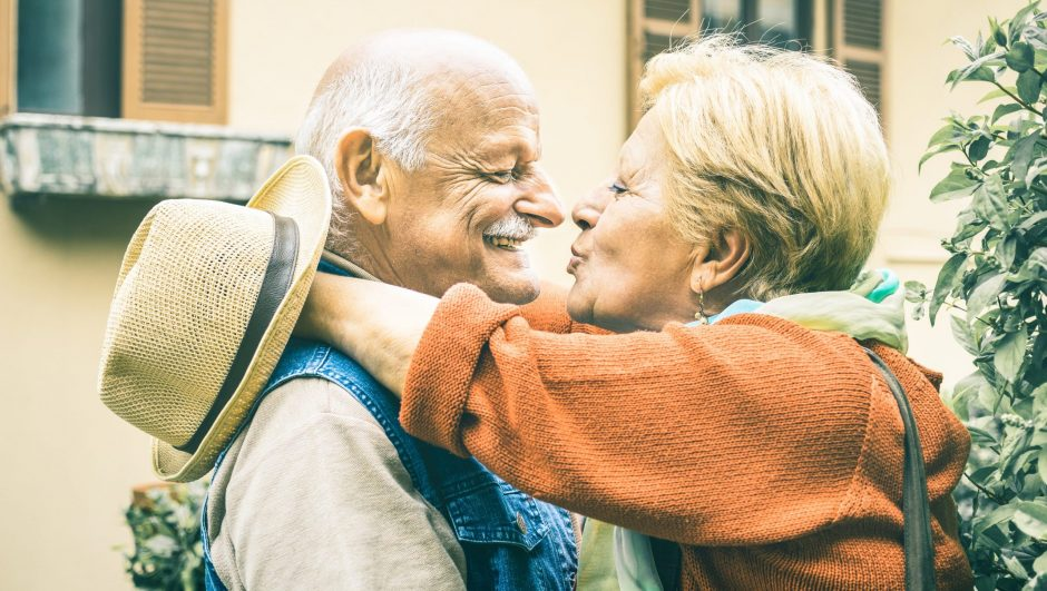 Happy senior retired couple having fun kissing outdoors