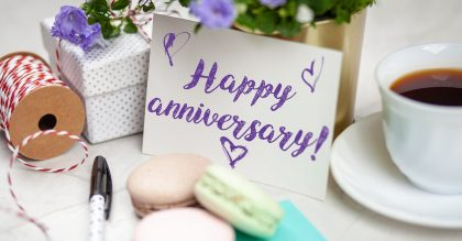 Writing a Happy Anniversary postcard on white marble table