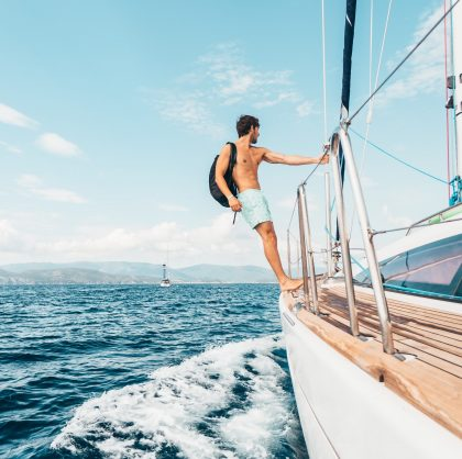 Man standing on edge of sailboat in Barcelona