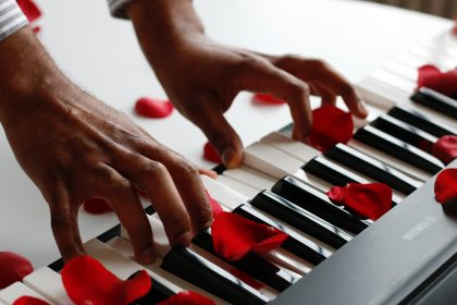 Hands playing rose covered piano