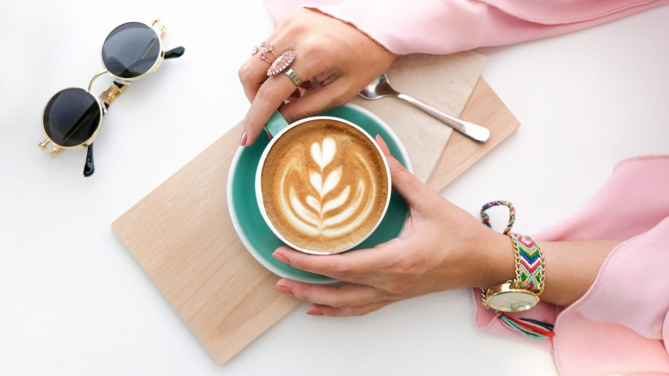 woman holding cup of latte