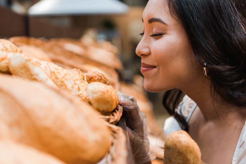 cheerful asian woman smiling while smelling bread in supermarket