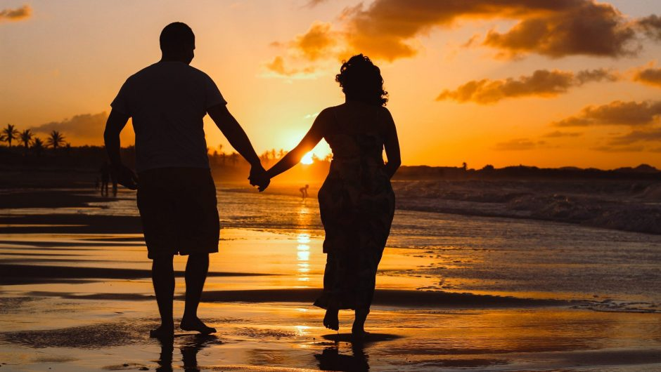 Couple walking on beach for 35th wedding anniversary