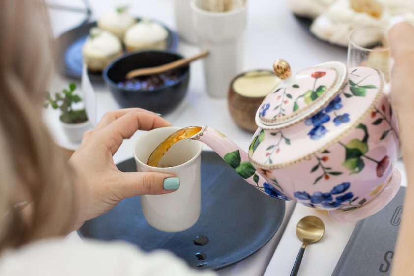 Tea being poured from porcelain tea pot at afternoon tea