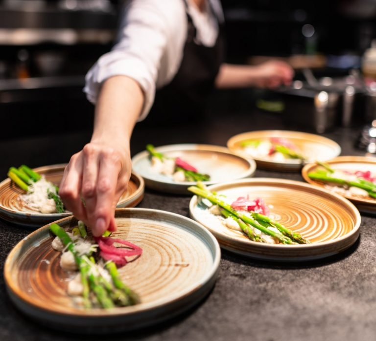 Female chef plating up food in a kitchen restaurant
