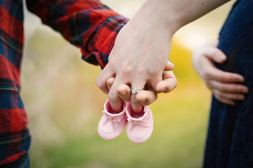 Expectant couple holding hands
