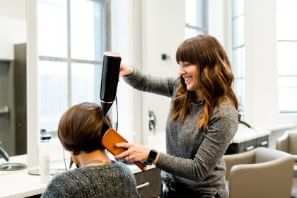 Hair dresser blow drying hair at a hair salon