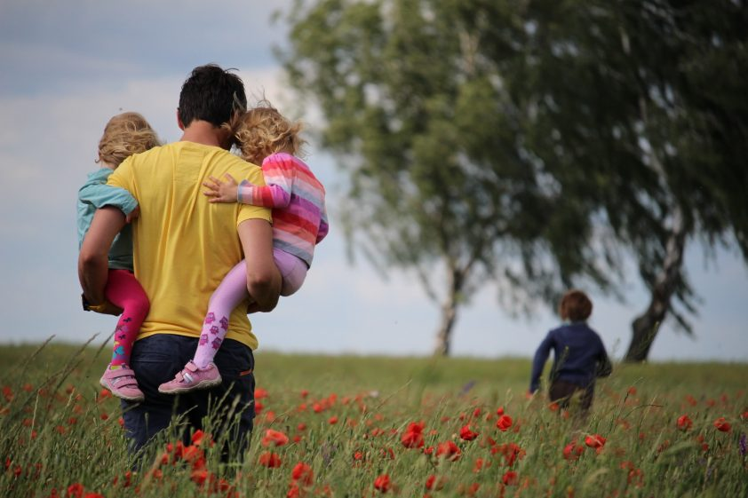 Dad with his daughters in a field of flowers
