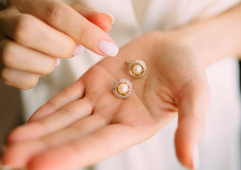 Woman touching pearl earrings to tell if real
