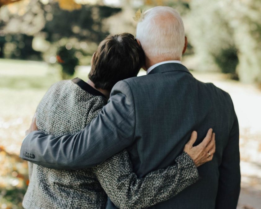 Older man and woman consoling each other