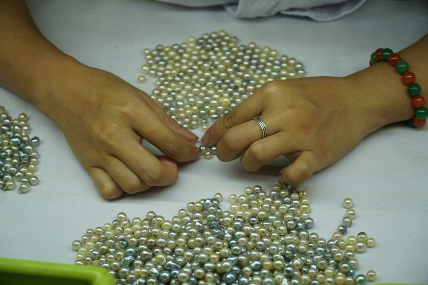 Woman handling real raw pearls