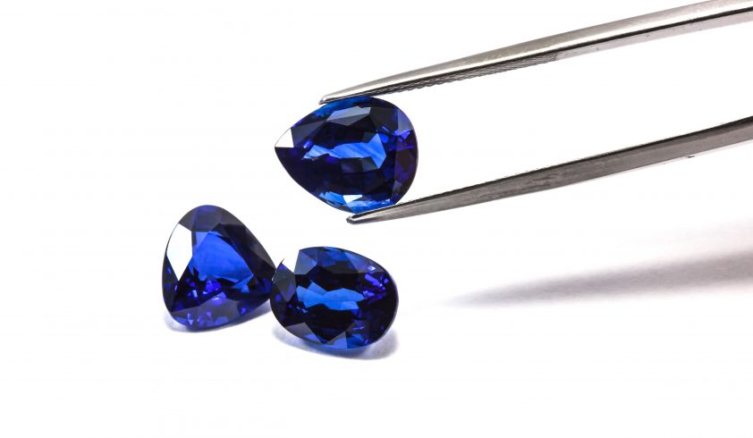 Group of the blue sapphires with tweezers