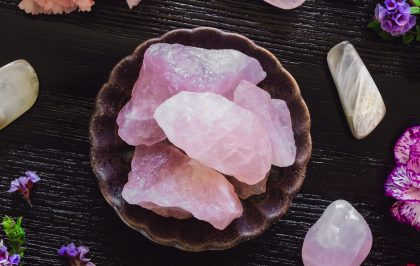 Rose Quartz and Moonstone on Dark Table with Carnations and Sea Lavender