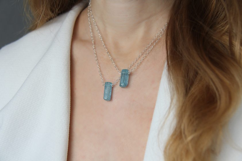 Crystal blue aquamarine pendant worn by woman