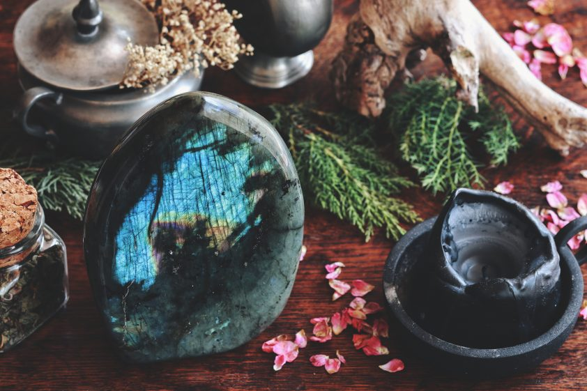 Labradorite crystal on dark wooden table with various nature objects like dried evergreens, plants, flowers, herbs in the background