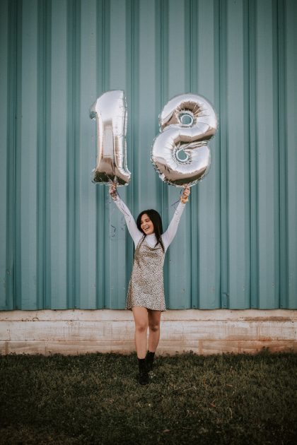 Girl holding 18th birthday balloons