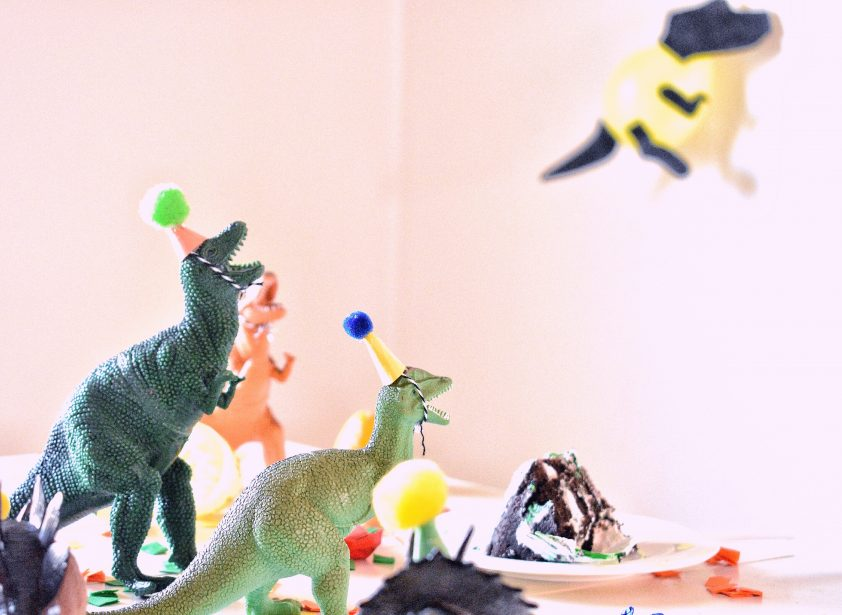 Toy dinosaurs wearing birthday hats