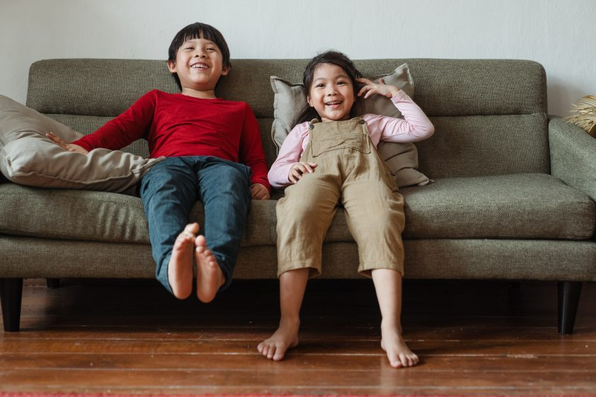 Siblings laughing on the couch