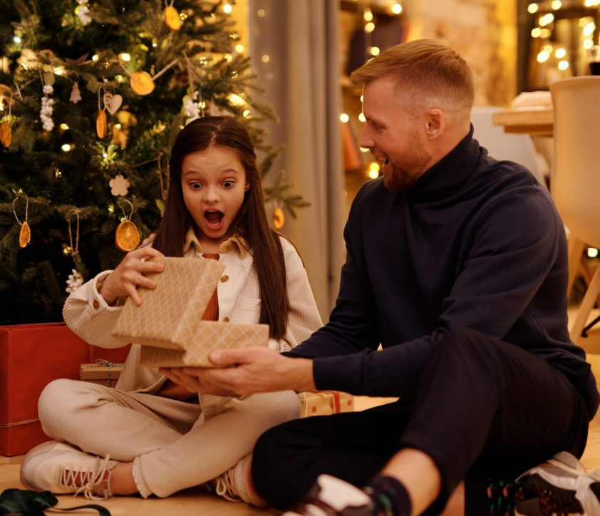 Surprised girl opening her Christmas gift