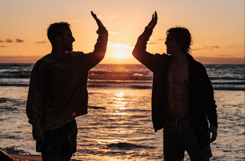 Brothers-in-law high-fiving on beach