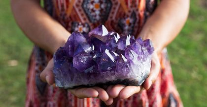A young woman holds a large cluster of amethyst crystals as they shimmer in the sunlight.