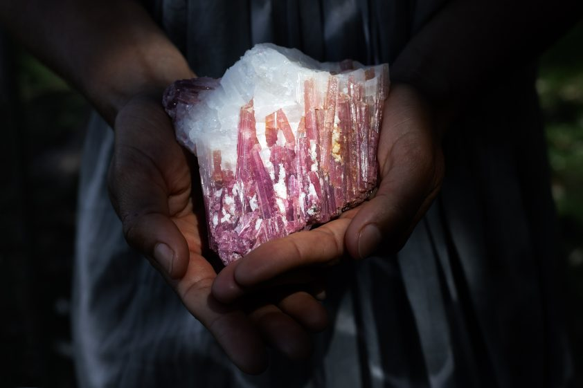 Woman holding pink tourmaline in quartz crystal in powerful healing concept