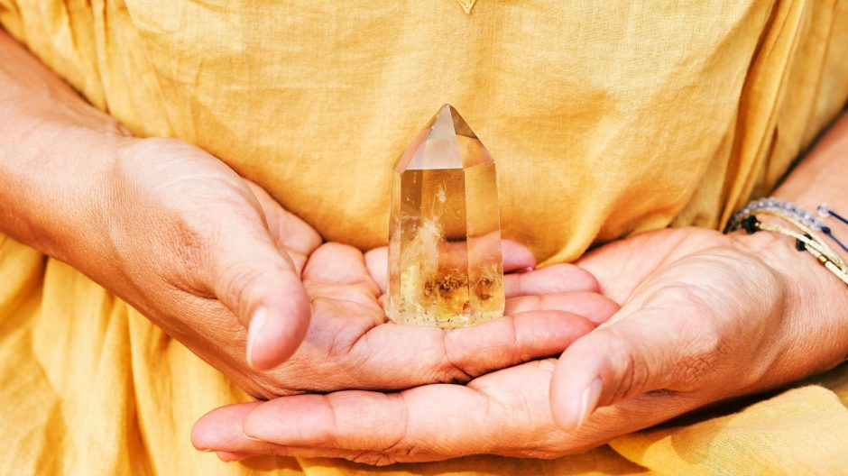 Close up image of Citrine crystal held by a woman