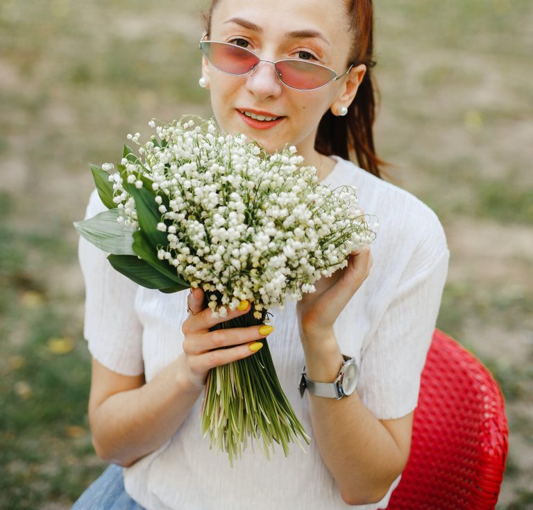 Girl holding a birthday bouquet of lily of the valley flowers