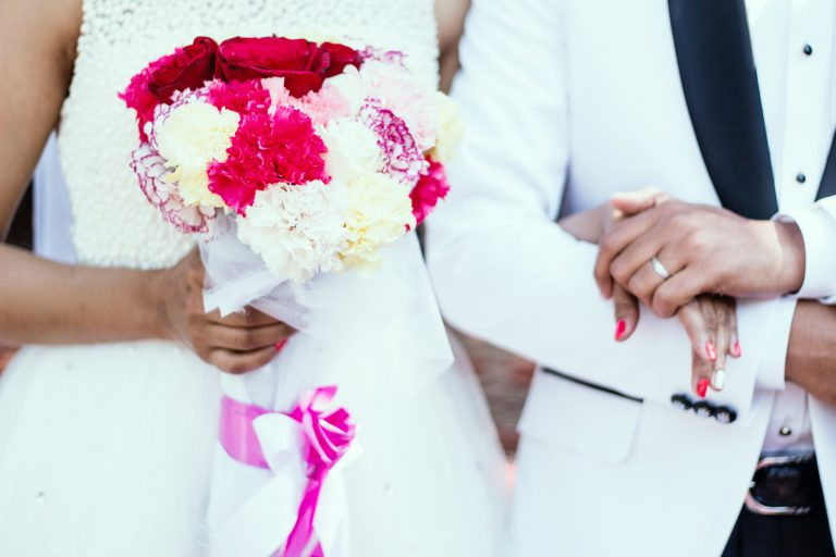 Bride holding a bouquet of brightly coloured carnations