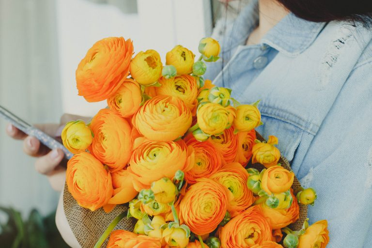 a girl holding a bunch of bright yellow ranunculus