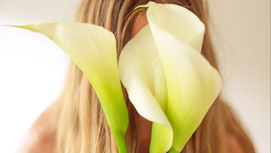 calla lily flowers covering the face of a woman