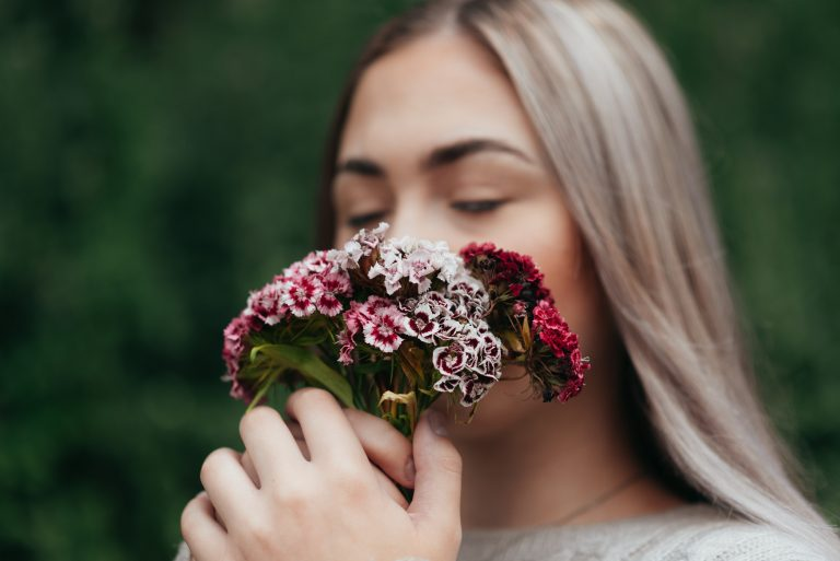 a girl holding and smelling dianthus flowers