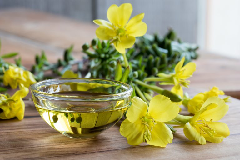 Evening primrose oil in a glass bowl, with fresh evening primrose flowers in the background
