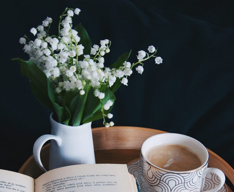Vase of lily of the valley flowers next to book and coffee