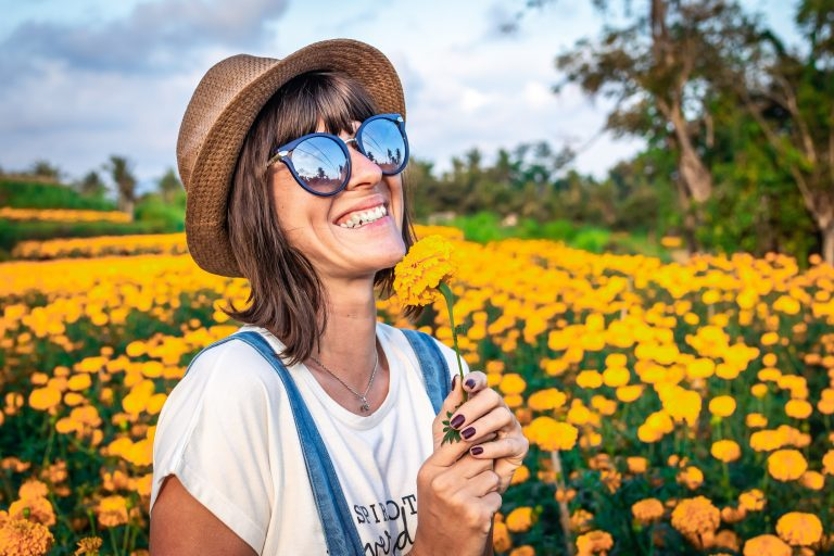 A woman holding a marigold smiling in a field of marigolds