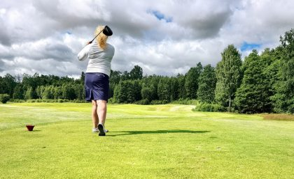 Woman teeing off on her birthday golf holiday